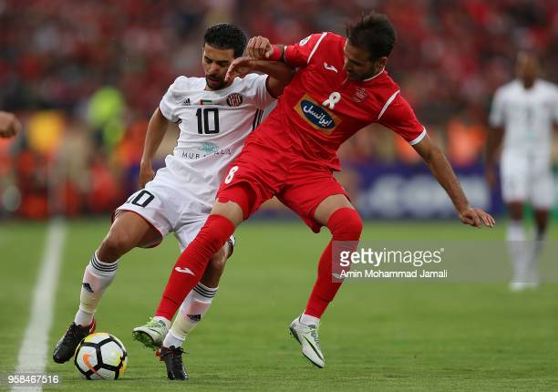Mbark Boussoufa of Al Jazira and Ahmad Noorollahi in action during AFC Champions League match between Persepolis and Al Jazira at Azadi Stadium on...