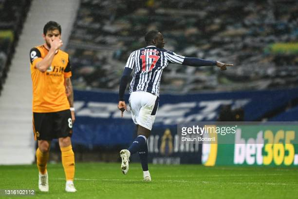 Mbaye Diagne of West Bromwich Albion celebrates after scoring their side's first goal as Ruben Neves of Wolverhampton Wanderers looks dejected during...