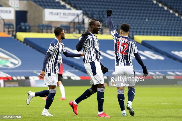 Mbaye Diagne of West Bromwich Albion celebrates with team mate Ainsley Maitland-Niles and Matheus Pereira after scoring their side's first goal...