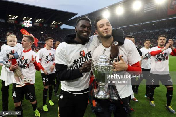 Mbaye Niang and Rami Bensebaini of Rennes with the trophy during the Ligue 1 match between Rennes and Monaco on May 1 2019 in Rennes France
