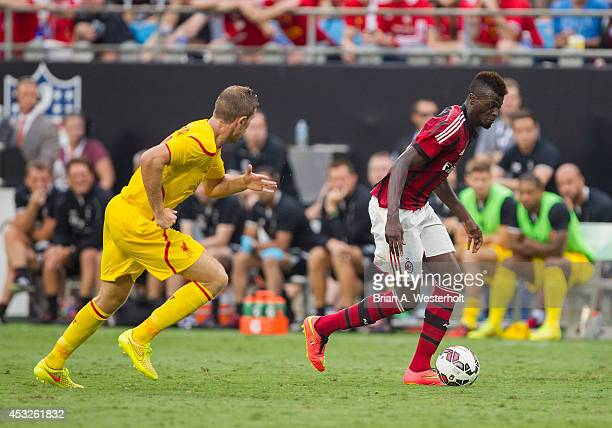 Mbaye Niang of AC Milan keeps the ball away from Lucas Leiva of Liverpool in the Guinness International Champions Cup at Bank of America Stadium on...
