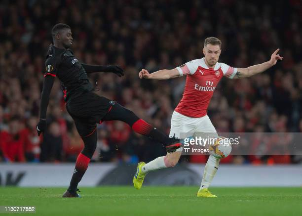 Mbaye Niang of Stade Rennes and Aaron Ramsey of Arsenal battle for the ball during the UEFA Europa League Round of 16 Second Leg match between...