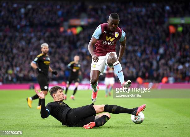 Mbwana Samatta of Aston Villa is challenged by John Stones of Manchester City during the Carabao Cup Final between Aston Villa and Manchester City at...