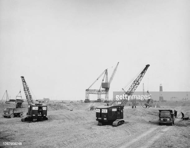 McAlpine cranes clearing the soft shingle 'spoil' at Dungeness in Kent, during the construction of Britain's sixth nuclear power station, February...