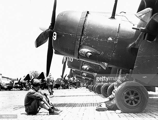 Mécaniciens de l'aéronavale assis sous des bombardiers participant à l'appui des troupes au sol engagées dans la bataille de Diên Biên Phu, sur la...