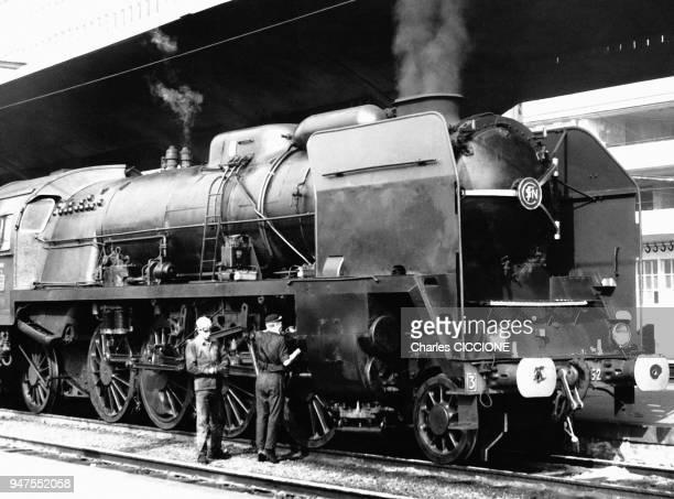 Mécaniciens inspectant une locomotive à vapeur 141P de la SNCF en France