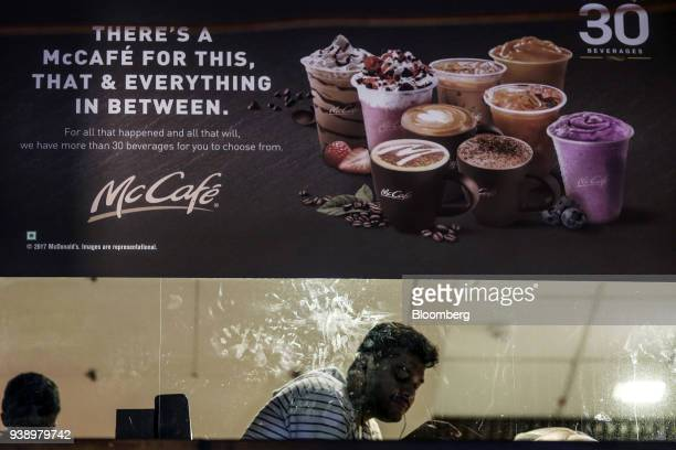 McCafe menu items are advertised in the window of a McDonald's Corp restaurant operated by Hardcastle Restaurants Pvt in Mumbai India on Tuesday...