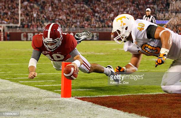 McCarron of the Alabama Crimson Tide scores a touchdown as he dives against Austin Johnson of the Tennessee Volunteers at BryantDenny Stadium on...