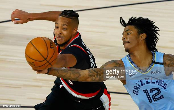 McCollum of the Portland Trail Blazers and Ja Morant of the Memphis Grizzlies go after a rebound during the fourth quarter in the Western Conference...