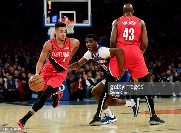 McCollum of the Portland Trail Blazers drives past Damyean Dotson of the New York Knicks during the first half of their game at Madison Square Garden...