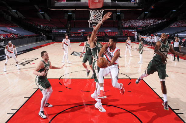 McCollum of the Portland Trail Blazers drives to the basket and looks to pass the ball during the game against the Milwaukee Bucks on April 2 2021 at...
