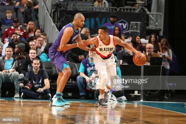 McCollum of the Portland Trail Blazers handles the ball against Nicolas Batum of the Charlotte Hornets on December 16 2017 at Spectrum Center in...