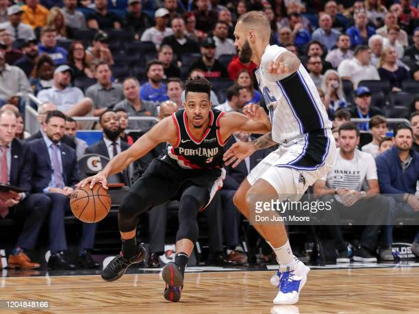 J McCollum of the Portland Trail Blazers is defended by Evan Fournier of the Orlando Magic while driving to the basket during the game at the Amway...