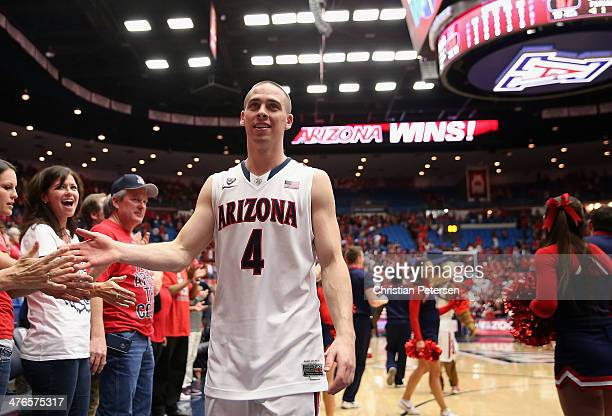 J McConnell of the Arizona Wildcats highfives fans as he walks off the court following the college basketball game against the California Golden...