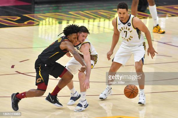 McConnell of the Indiana Pacers steals the ball from Collin Sexton of the Cleveland Cavaliers as Malcolm Brogdon looks on during the fourth quarter...