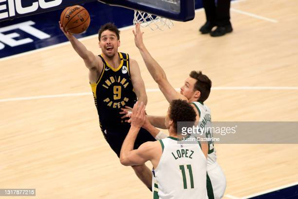McConnell of the Indiana Pacers takes a shot while guarded by Pat Connaughton and Brook Lopez of the Milwaukee Bucks during the third quarter at...