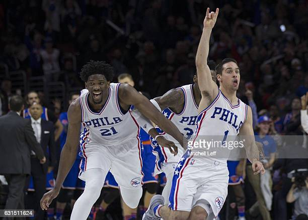 J McConnell of the Philadelphia 76ers celebrates with Joel Embiid and Robert Covington after making the game winning shot at the buzzer against the...