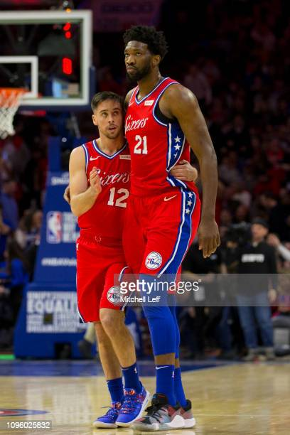 J McConnell of the Philadelphia 76ers hugs Joel Embiid at the end of the first quarter against the Denver Nuggets at the Wells Fargo Center on...
