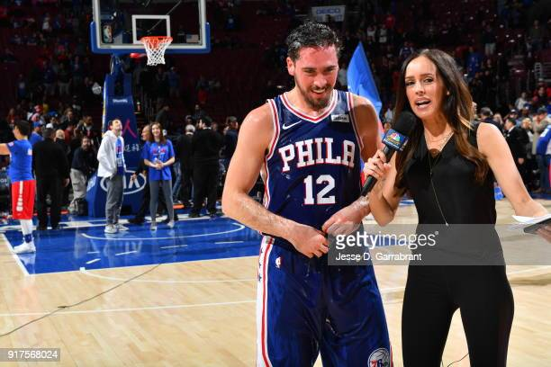 J McConnell of the Philadelphia 76ers is interviewed by Molly Sullivan while Joel Embiid and Robert Covington pours water over him in congratulations...