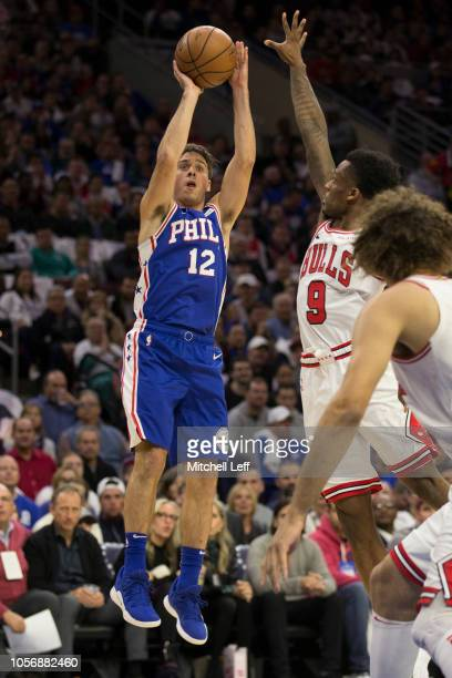 J McConnell of the Philadelphia 76ers shoots the ball against Antonio Blakeney of the Chicago Bulls at the Wells Fargo Center on October 18 2018 in...