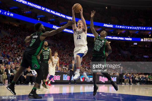 J McConnell of the Philadelphia 76ers shoots the ball against Jaylen Brown and Terry Rozier of the Boston Celtics in the fourth quarter during Game...