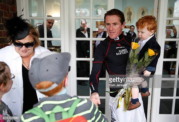 AP McCoy with his son Archie gets flowers from wellwishers outside the weighing room before racing during AP McCoy's final day of riding before...