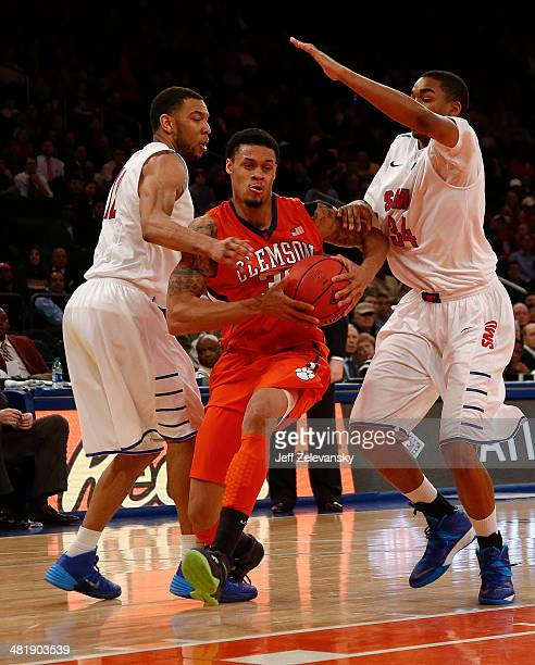 J McDaniels of the Clemson Tigers drives by Ben Moore of the Southern Methodist Mustangs during the NIT Championship semifinals at Madison Square...