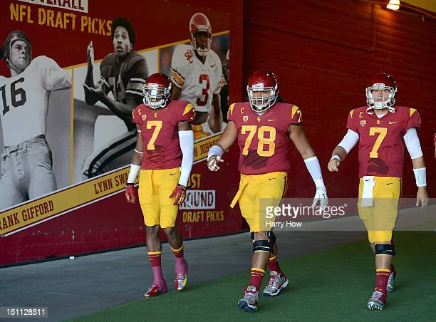 J McDonald Khaled Holmes and Matt Barkley of the USC Trojans makes their way to the field before the game against the Hawaii Warriors at Los Angeles...