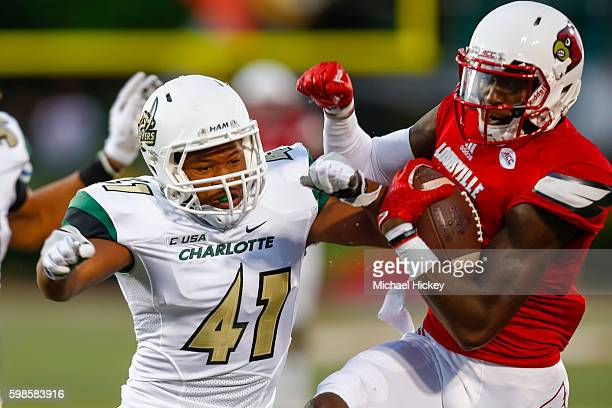 McDonald of the Charlotte 49ers makes the hit on Jamari Staples of the Louisville Cardinals as he runs the ball at Papa John's Cardinal Stadium on...