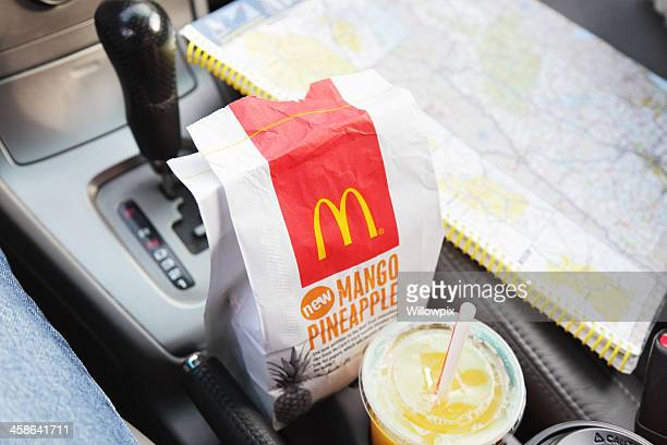 mcdonald's breakfast bag and orange juice in car with roadmap - mcdonald's stock pictures, royalty-free photos & images