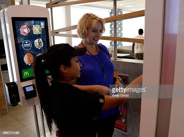McDonalds concierge/server Jacqueline Garcia left helps customer Jan Ferrell order a custom meal from the the Create Your Taste kiosk at 4000 S...