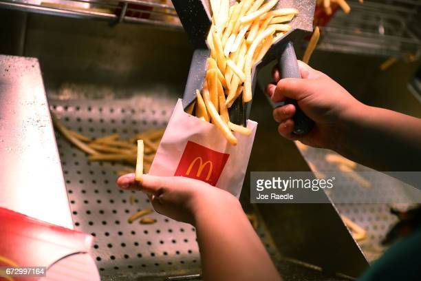 McDonald's crew member Samantha Medina prepares french fries as the McDonald's restaurant stock price reached record territory on April 25, 2017 in...