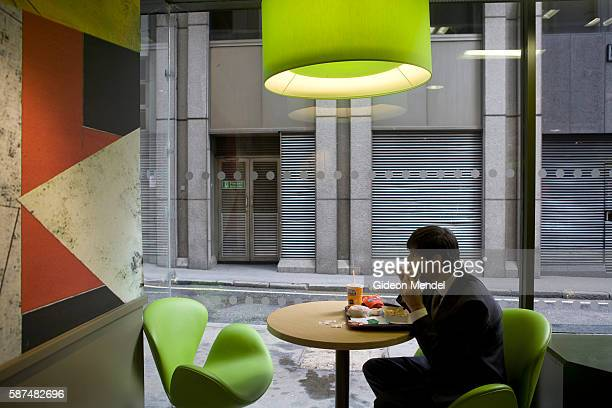 A McDonald's customer tucks into his Big Mac oblivious to the new trendy coffee bar style ambience and design at the Cannon Street branch of...