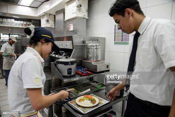 A McDonald's employee helps prepare a meal with rice and beans for a coworker at a McDonald's Corp restaurant in Barueri Brazil on Tuesday April 29...
