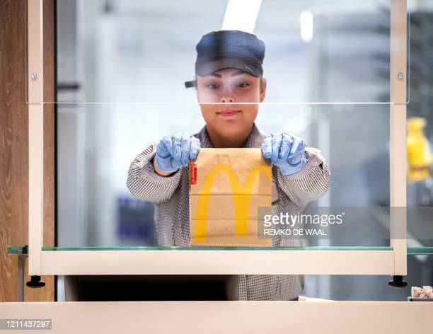 McDonalds' employee holds up a food package at a test location in a restaurant at The GelreDome Arnhem, The Netherlands on May 1 as part of measures...