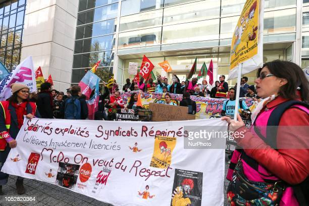 McDonald's employees and union members hold a banner reading « Exploited workers McDo we want to be respected » as they protest against the tax...