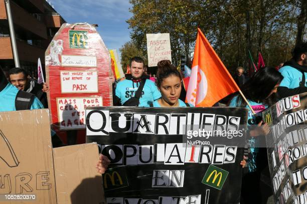 McDonald's employees and union members hold placard reading « Popular districts in revolt » as they protest against the tax evasion and the low...