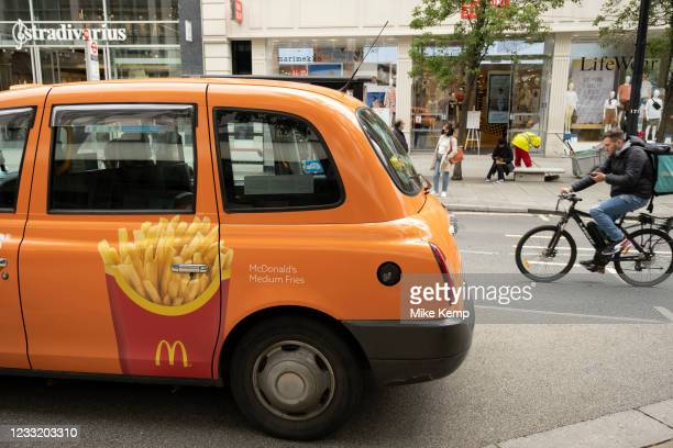 McDonald's medium fries emblazoned on the side of an orange taxi on 25th May 2021 in London, United Kingdom. McDonald's Corporation is an American...
