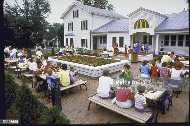 McDonald's restaurant is seen from outside where people eat outdoors at picnic tables The building's exterior has an unusal classic country inn look