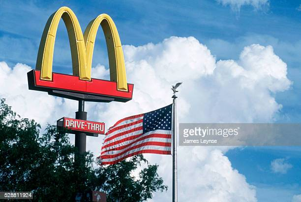 McDonald's restaurant sign in the sky next to the American flag