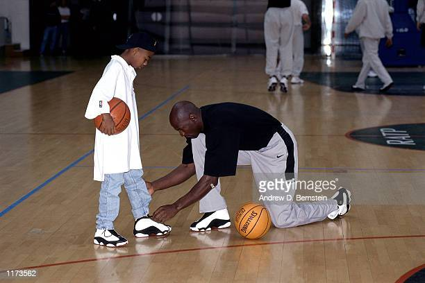 McDonald's Tournament Michael Jordan of the Chicago Bulls ties his son's shoelaces at a Mcdonald's tournament practice in Paris France NOTE TO USER...