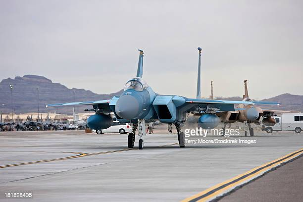 McDonnell Douglas F-15C Eagles of the 57th Adversary Tactics Group, taxi to the runway at Nellis Air Force Base, Nevada.