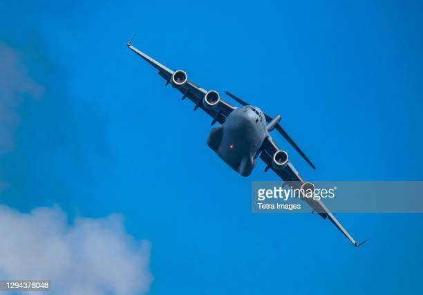 mcdonnell douglas/boeing c-17 globemaster iii american air force cargo plane flying against sky - mcdonnell douglas c 17 globemaster stock pictures, royalty-free photos & images