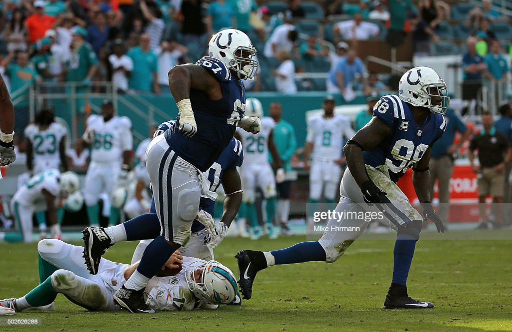 T.Y. McGill #67 and Robert Mathis #98 of the Indianapolis Colts celebrate sacking Ryan Tannehill #17 of the Miami Dolphins during a game at Sun Life Stadium on December 27, 2015 in Miami Gardens, Florida.