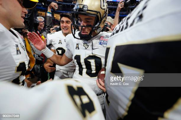McKenzie Milton of the UCF Knights celebrates with teammates after defeating the Auburn Tigers 3427 to win the ChickfilA Peach Bowl at MercedesBenz...