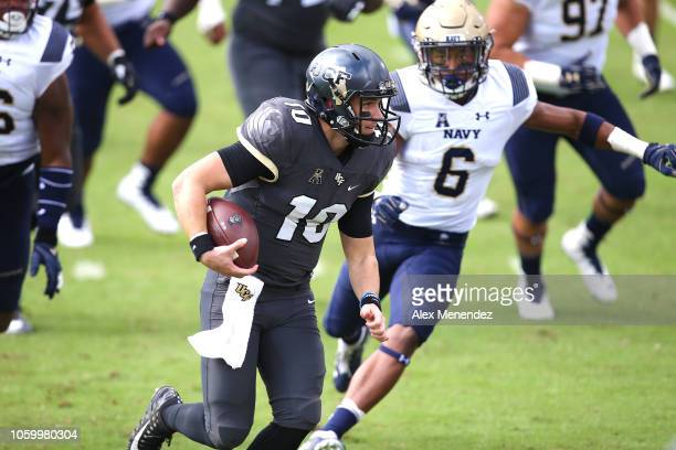 McKenzie Milton of the UCF Knights is chased by Sean Williams of the Navy Midshipmen during a game between the Navy Midshipmen and the UCF Knights at...