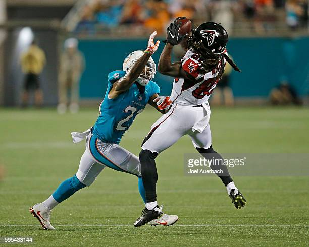D McKissicook of the Atlanta Falcons catches the ball while being defended by Jordan Lucas of the Miami Dolphins during a preseason game on August 25...