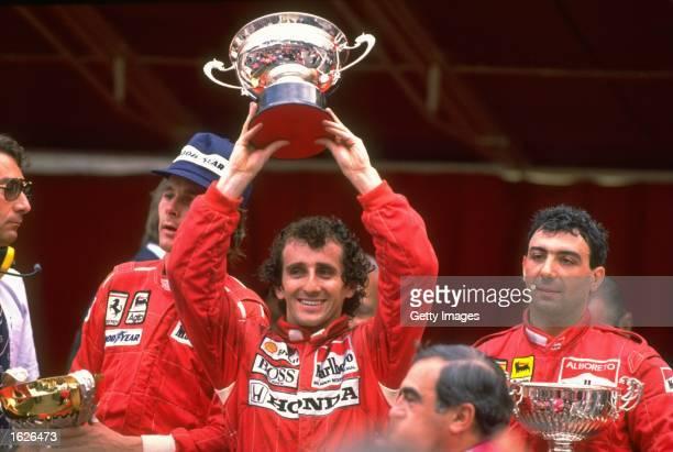 McLaren Honda driver Alain Prost of France holds the trophy aloft flanked by Scuderia Ferrari drivers Gerhard Berger of Austria and Michele Alboreto...