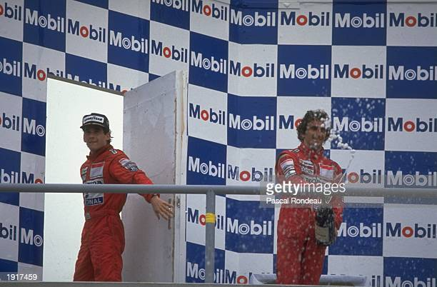 McLaren Honda driver Alain Prost of France stands on the winner's podium spraying Champagne as team mate Ayrton Senna of Brazil walks off after the...