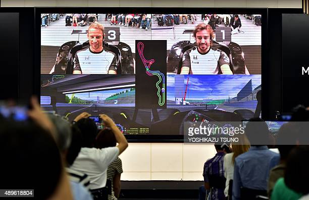 McLaren Honda Formula One drivers Fernando Alonso and Jenson Button play racing video games in front of an audience of Japanese fans at the Honda...